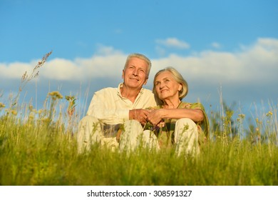 Portrait of happy elderly couple  on nature at summer