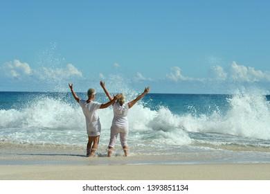 Portrait of happy elderly couple resting on beach waving hands