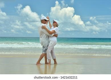 Portrait of happy elderly couple resting on beach dancing