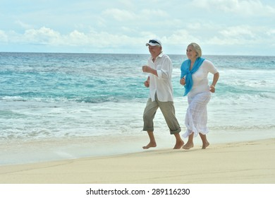 Portrait of a happy elderly couple running  on beach