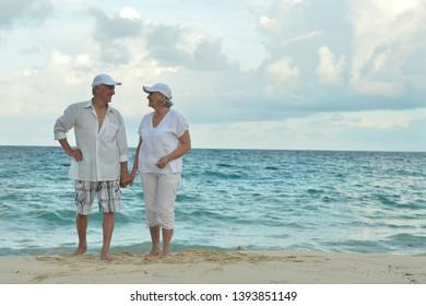 Portrait of happy elderly couple standing on tropical beach