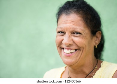 Portrait of happy elderly hispanic lady smiling at camera. Copy space
