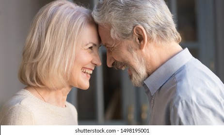 Portrait of happy elderly husband and wife touch foreheads look in eyes enjoy intimate romantic moment together, smiling mature couple having close tender time at home, lovers reunited at old age