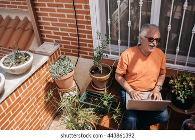 Portrait of happy elderly man sitting on bench with laptop and looking down