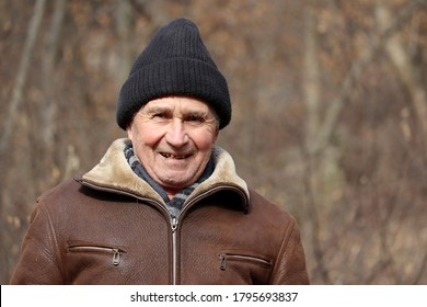 Portrait of happy elderly man standing in autumn park. Concept of old age, life in village