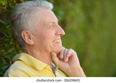 Portrait of happy elderly man in summer park