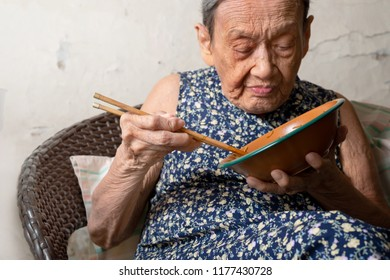Portrait of a happy elderly woman in colorful dress  eating noodle with chopsticks by herself.90 up of healthy woman having lunch,front view.