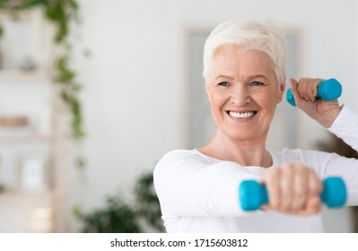 Portrait Of Happy Elderly Woman Exercising With Dumbbells At Home, Having Active Lifestyle On Retirement, Smiling At Camera, Copy Space