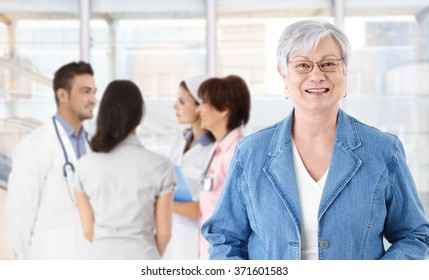 Portrait of happy elderly woman in glasses. Medical team in background.