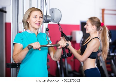 Portrait of happy elderly and young women doing powerlifting on machines in jym