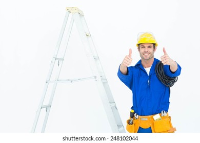 Portrait of happy electrician gesturing thumbs up while standing by ladder over white background