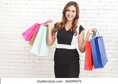 portrait of happy elegant woman carrying multicolor shopping bags on white brick wall background