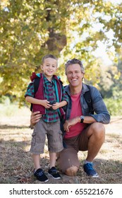 Portrait of happy elementary boy and father in forest
