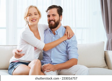 Portrait of happy embracing couple sitting on the sofa
