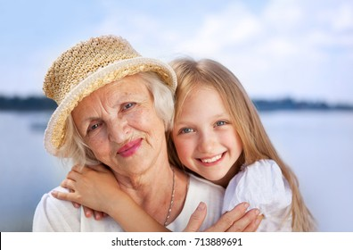 Portrait of Happy Embracing Grandmother and Granddaughter looking at the Camera at the Sunny Summer Day