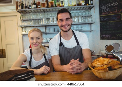 Portrait of happy employees standing together at counter in cafe