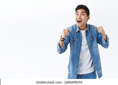 Portrait of happy energized young excited asian man watching sports game on tv in pub, cheering for team scored goal, smiling pleased, clench fists in victory, success gesture, triumphing