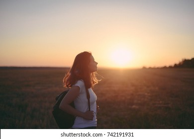 Portrait of happy and enjoying young woman on a meadow on a sunset. Cheerful girl on sunset. Lifestyle and happiness concept.