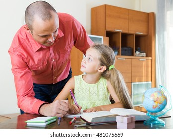 Portrait of happy european dad helping schoolgirl to study at home