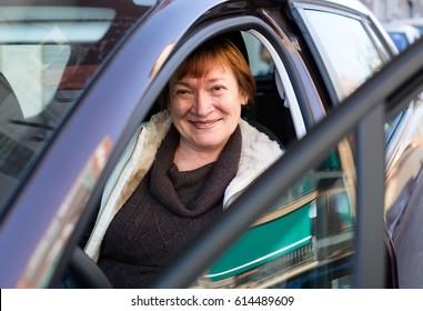 Portrait of happy european female senior driver smiling in car