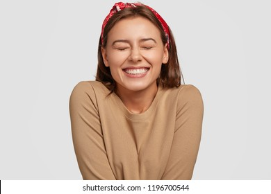 Portrait of happy European woman has broad smile, closes eyes, feels excitement, being in high spirit, recieves proposal from boyfriend, laughs at something funny, models against white background