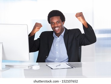 Portrait Of A Happy Excited African Man Sitting In Front Of Desktop