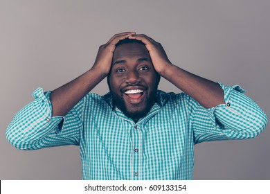Portrait of happy excited afroamerican  bearded  man holding head and open mouth.