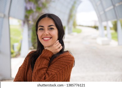 Portrait of happy excited Asian girl adjusting hair. Positive young woman in knitted sweater looking at camera. Woman on stroll concept