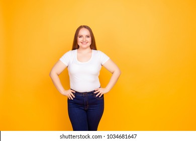 Portrait of happy excited cheerful confident with beaming toothy smile fatty woman wearing white tshirt and jeans, she is holding her hands on hips, isolated on bright yellow background