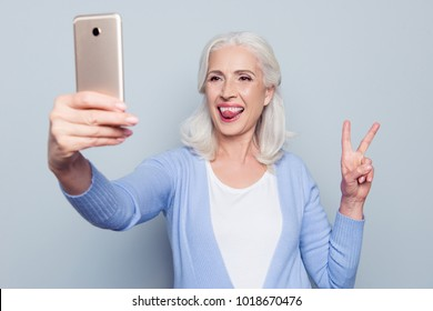 Portrait of happy excited cheerful joyful funny grandmother grandma granny showing tongue and two fingers and taking self portrait on her mobile phone, isolated on gray background