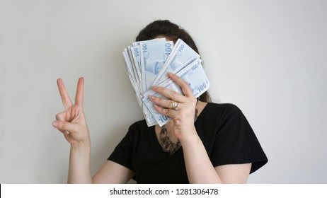 Portrait of a happy excited cheerful young woman holding bunch of Turkish Lira money banknotes. Celebrating first wage isolated on white background. Lucky girl showing victory sign / great / good sign