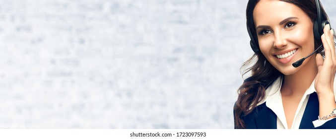 Portrait of happy excited confident customer support female phone operator in headset, against white brick wall background. Consulting and assistance service call center.