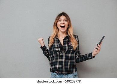 Portrait of a happy excited girl holding mobile phone and celebrating win isolated over grey background