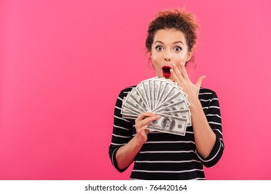 Portrait of a happy excited girl holding bunch of money banknotes and looking at camera isolated over pink background