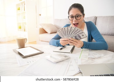 portrait of happy excited successful young business woman holding money dollar bills and looking at cash feel surprised sitting at living room. Positive emotion facial expression feeling.