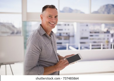 Portrait of happy executive using digital tablet in office