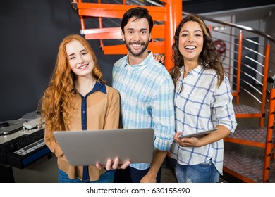 Portrait of happy executives holding laptop and digital tablet in office
