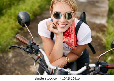 Portrait of happy extremal young woman with shining smile, dressed in fashionable biker`s clothing, rests on fast motorbike, likes her hobby. People, active lifestyle and extreme sport concept