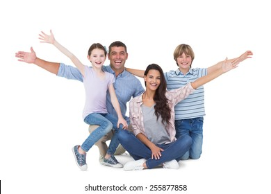 Portrait of happy family with arms outstretched over white background