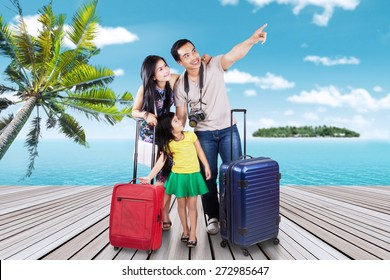 Portrait of happy family arriving at the pier of the resort island while carrying their suitcase