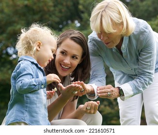 Portrait of a happy family with baby mother and grandmother outdoors