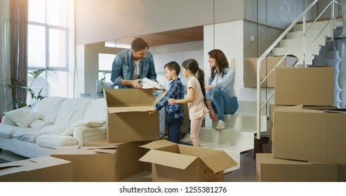Portrait of happy family bought new house  and unpacking boxes for moving into. Concept of mortgage, insurance, property, real estate.