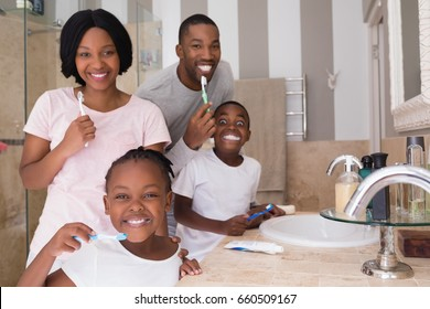 Portrait of happy family brushing teeth in bathroom at home