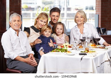 Portrait of a happy family with children and grandparents at the dining table