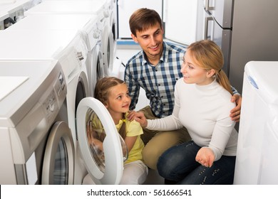 portrait of happy family choosing laundry washer in appliance store