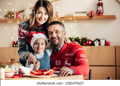 portrait of happy family with daughter in christmas hat sitting at table with holiday dinner