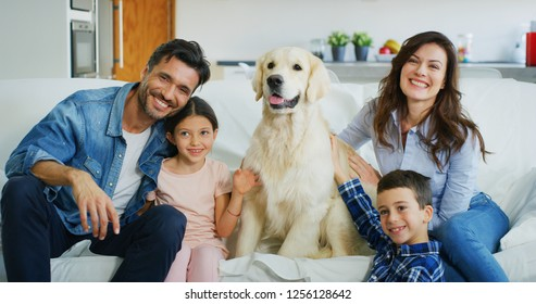Portrait of happy family with a dog having fun together in living room. Concept of happy family, love for animals, childhood