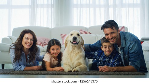 Portrait of happy family with a dog having fun lying on the carpet in living room. Concept of happy family, love for animals, pedigree pet