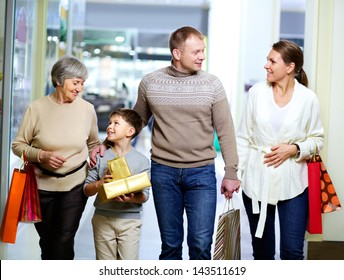 Portrait of happy family during shopping in the mall