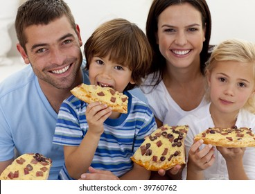 Portrait of happy family eating pizza in living-room all together